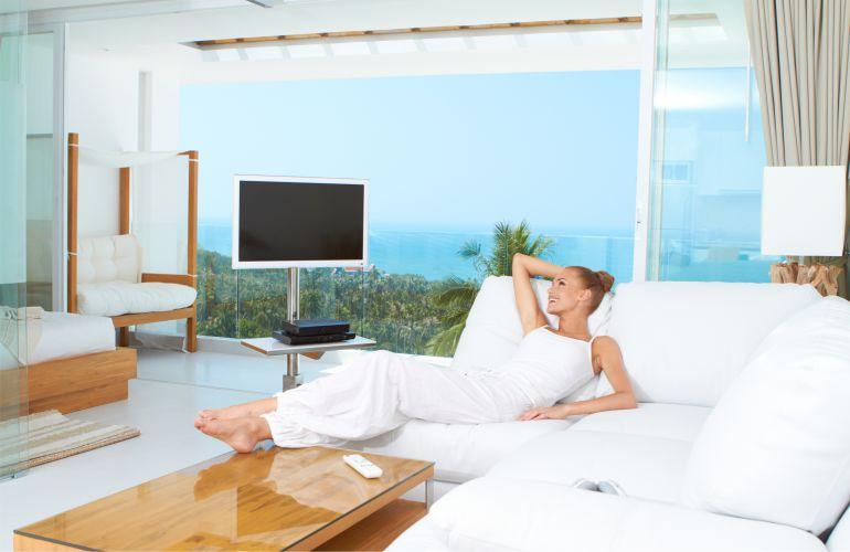 Купить недвижимость в Майами - фото красивая девушка лежит на диване в квартире с видом на океан